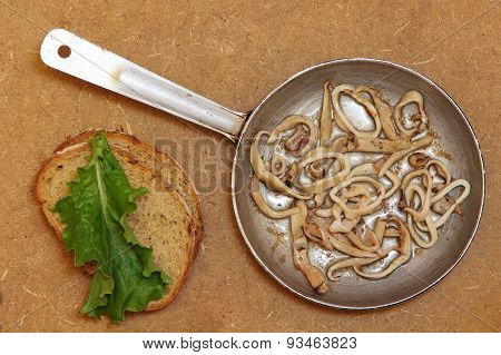 Roasted Squids Pieces In Frying Pan And Bread Slices.top View.