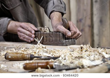 Hands Of Carpenter Plane On The Workbench In Carpentry