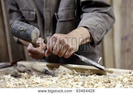 Hands Of Carpenter With A Hammer And Chisel On The Workbench In Carpentry