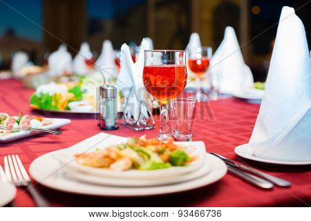 Festively served banquet table with glasses and salads.