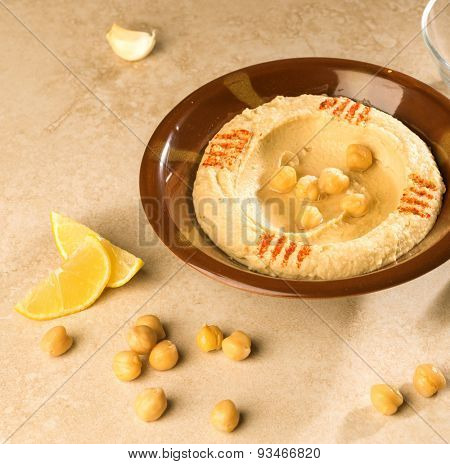 Bowl of Hummus with raw chickpeas and lime wages.