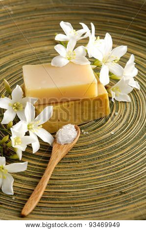 gardenia flower with soap, salt in spoon in wooden bowl