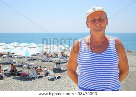 Portrait of elderly man in a striped vest and a white cap on the beach near the sea