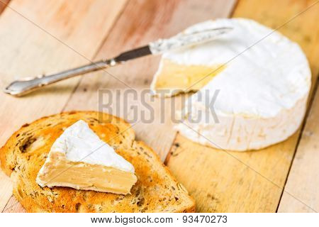 Camembert Cheese With Cut Wedge On Toasted Bread Slice And Vintage Knife On Wooden Table