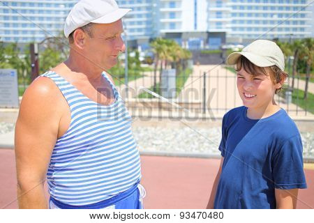Elderly man and young boy near the resort hotel