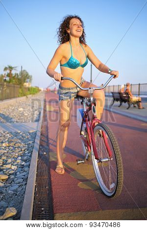 Beautiful young woman in a blue swimsuit riding a bike along the embankment at sunset