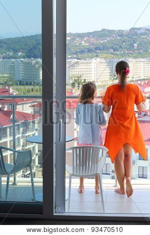 Young woman in an orange dress and daughter on the balcony in the room