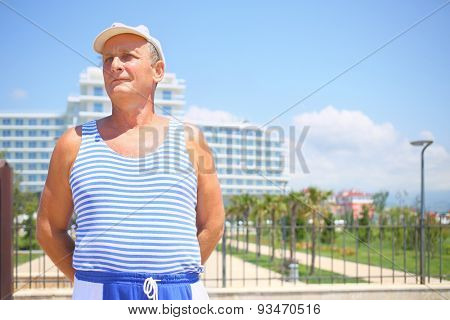 Portrait of elderly man in a striped vest and a white cap in front of the resort hotel