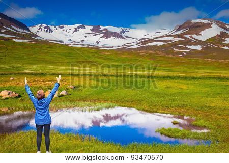 Blue lake water reflects the snowy hills. Iceland. The woman - tourist in blue jacket raised her hands in delight beauty of nature