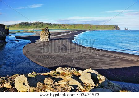 On an ocean beach with volcanic sand is a huge rock. Cape Dirholaey in southern Iceland