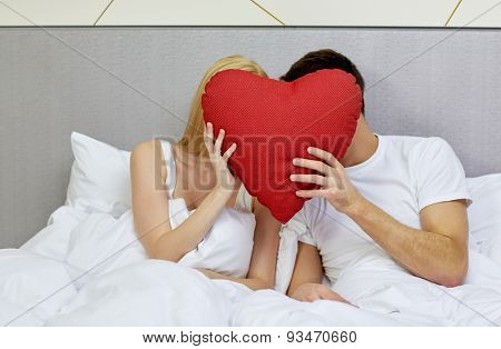 travel, love, valentines day, holidays and happiness concept - happy couple in bed hiding faces behind red heart shape pillow at hotel or home
