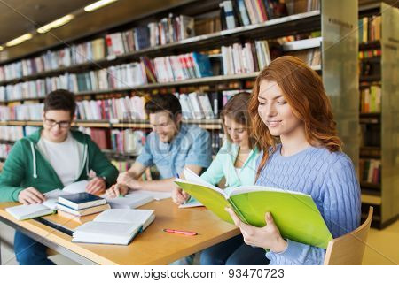 people, knowledge, education, literature and school concept - happy students reading books and preparing to exams in library