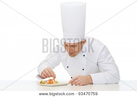 cooking, profession, haute cuisine, food and people concept - happy male chef cook decorating dish