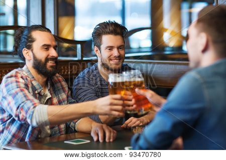 people, men, leisure, friendship and celebration concept - happy male friends drinking beer and clinking glasses at bar or pub