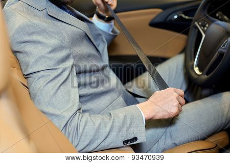 safety, driving and people concept - close up of man in elegant business suit fastening seat safety belt in car