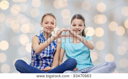 people, children, friends and friendship concept - happy little girls sitting and showing heart shape hand sign over holidays lights background