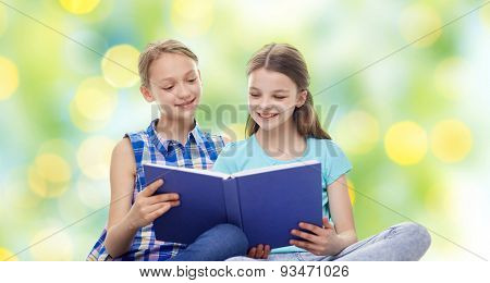 people, children, friends, literature and friendship concept - two happy girls sitting and reading book over green holidays lights background