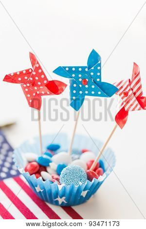 american independence day, celebration, patriotism and holidays concept - close up of glazed sweet candies with pinwheel toys decoration and american flag at 4th july theme party