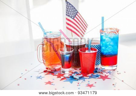 american independence day, celebration, patriotism and holidays concept - close up of drinks in cups and glasses with american flag on independence day party