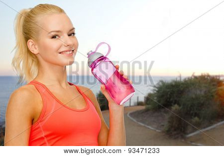people, sport, fitness, jogging and recreation concept - happy woman drinking water from bottle over beach sunset background