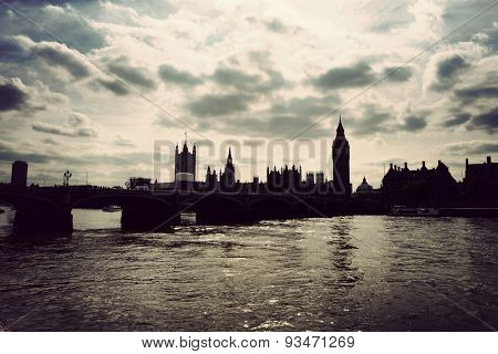 Silhouette of the Houses of Parliament, London with the River thames in the foreground under a cloudy sky in a tourism and travel concept