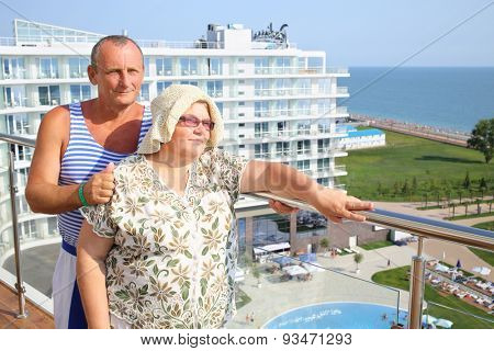 Portrait of elderly man in striped vest with wife on the terrace