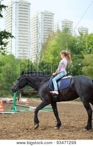 Young girl riding a horse in park near the apartment complex
