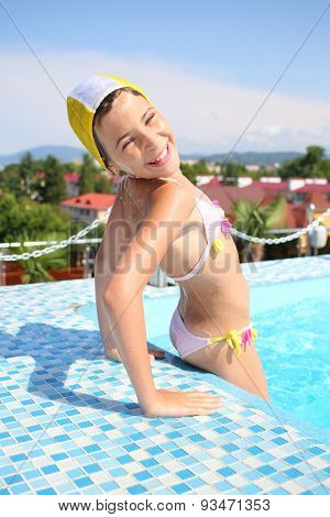 Portrait of a happy young girl in a bathing suit and swim cap in the pool