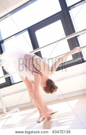 Young Ballerina Stretching At Barre In Studio