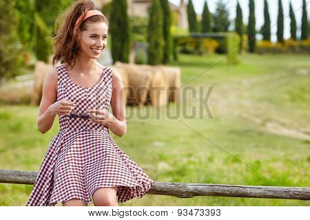 Outdoor fashion photo of the beautiful Italian woman brunette with curly hair in a summer dress