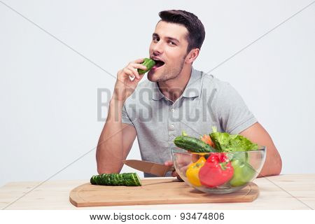 Man preparing salad and biting cucumber over gray background and looking at camera