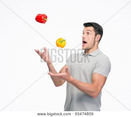 Young man juggling pepper isolated on a white background