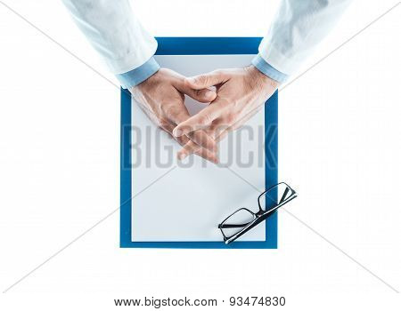 Doctor With Hands Clasped Waiting At Desk