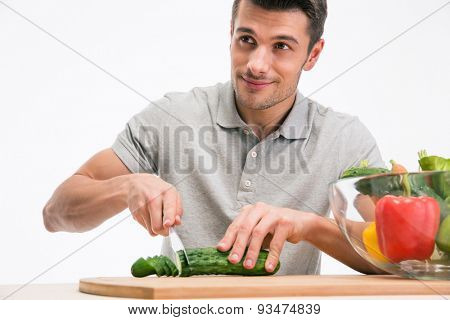 Happy man cutting cucumber and looking away isolated on a white background