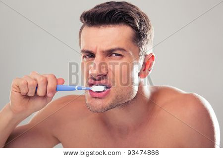 Portrait of a handsome man brushing his teeth over gray background and looking at camera