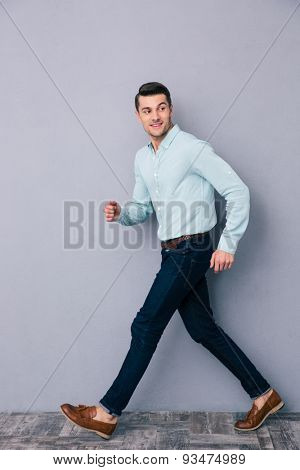 Happy young man walking over gray background and looking away