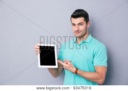 Happy young man showing blank tablet computer screen over gray background. Looking at camera