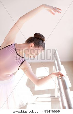 Ballerina Stretching At Barre In Dance Studio