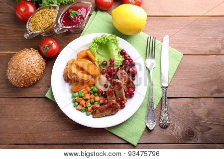 Beef with cranberry sauce, roasted potato slices, vegetables on plate, on  wooden background