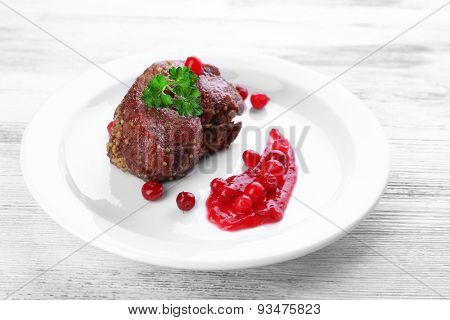 Tasty roasted meat with cranberry sauce on plate, on color wooden background
