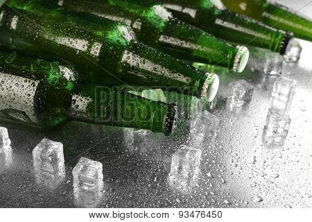 Glass bottles of beer with ice cubes on wet table background