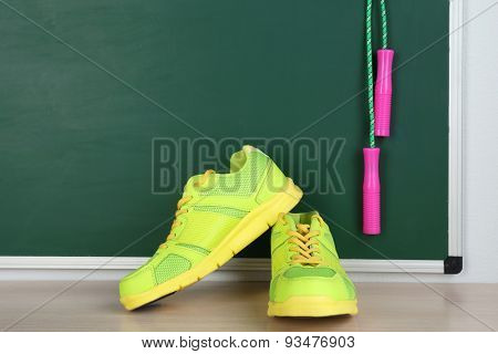Sport shoes and skipping rope on blackboard background