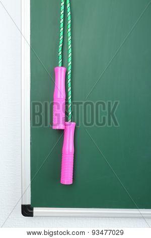 Skipping rope on green blackboard background