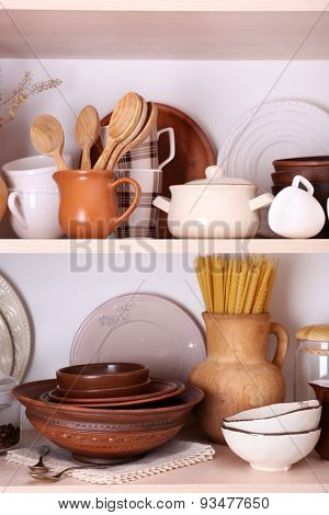 Kitchen utensils and tableware on wooden shelves
