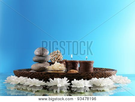 Spa still life with flowers and candlelight on blue background
