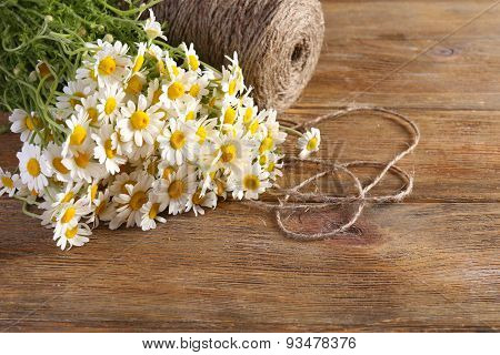 Beautiful bouquet of daisies with twine on wooden background