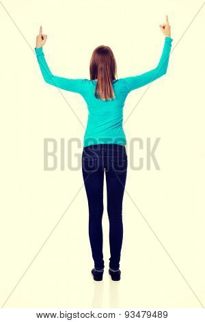 Happy teenage woman pointing up with both hands