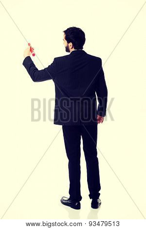 Handsome businessman writing with big red pencil.