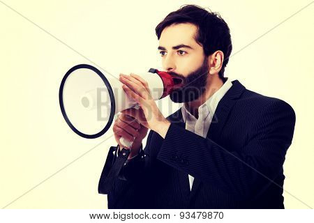 Handsome businessman shouting using a megaphone.