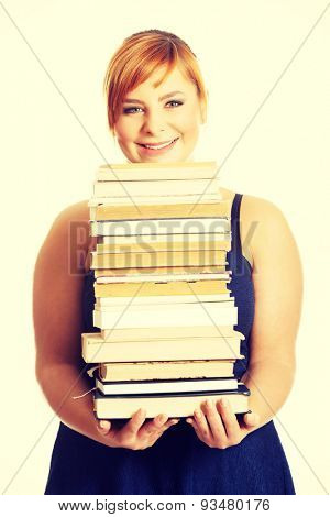 Overweight woman in skirt holding heavy books